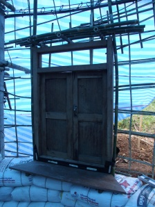 Old teak window sitting on rice-husk-bags, set in a bamboo frame attached to the 'bird cage'.