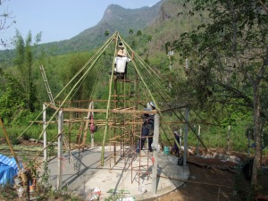 The first bamboo poles go up.  You can see the second roundhouse foundations behind, down the hill.