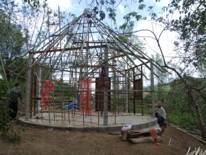 The 'birdcage' which will support both the thatch and rice-husk-bags.  Littlest worker is playing with an old cow bell hanging on a red string.