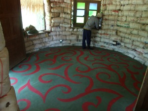 I used red acrylic roof paint for the design on this floor of polished green concrete.