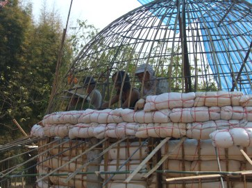 Thai team and volunteers attach the 'sausage' shaped rice husk bags of the domed ceiling onto the outside of the frame.