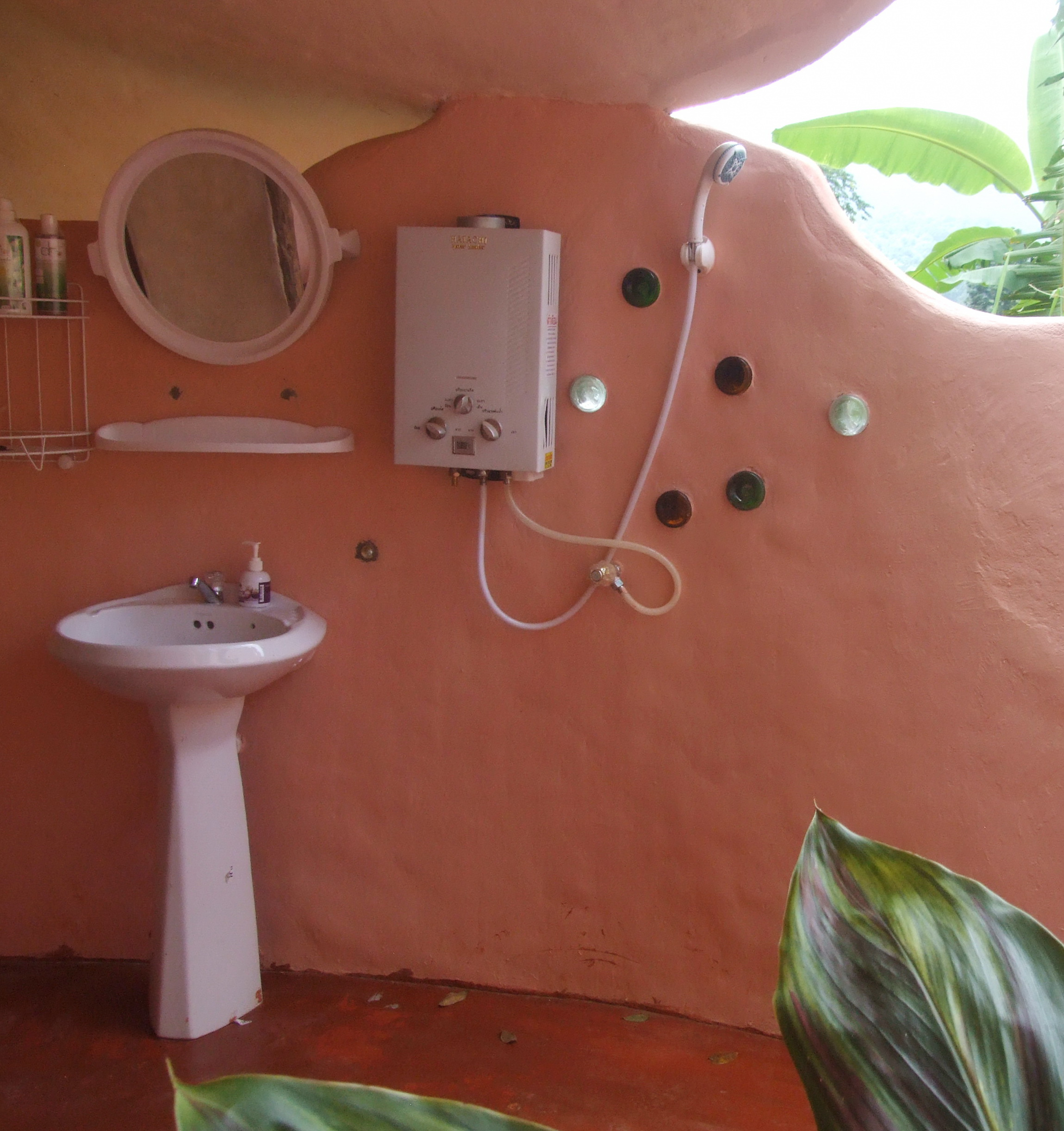 Glass bottles decorate the wall of this partially open air bathroom. August   2014   maggimck