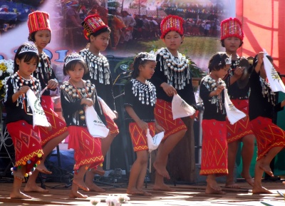 Young Kachin girls in ceremonial dress dance at a festival.