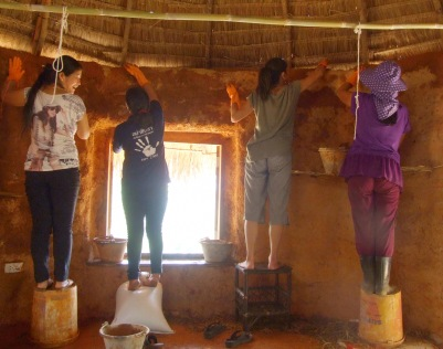 Women from the Nwai Pan Group visit Chiang Dao Roundhouses and have a go at plastering with mud.