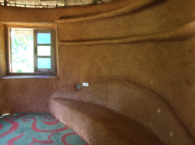 Bench made of earthbags, and shelves of bamboo, both covered with earth plaster.